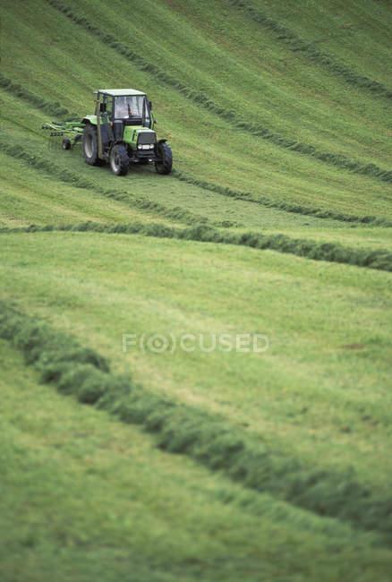 Agricultor, ajuntando campo de feno com trator em terras agrícolas da Baviera, Alemanha, Europa — Fotografia de Stock