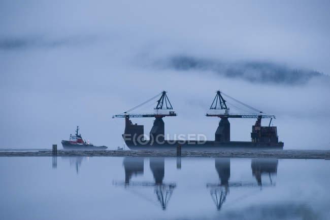 Краны поднимают и складывают бревна на поверхности палубы в Портлендском канале, порт Стюарт, Канада — стоковое фото