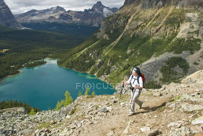 Mid adult woman hiking on Lake Ohara Alpine Circuit above Lake Ohara in Yoho National Park, British Columbia, Canada. — Stock Photo