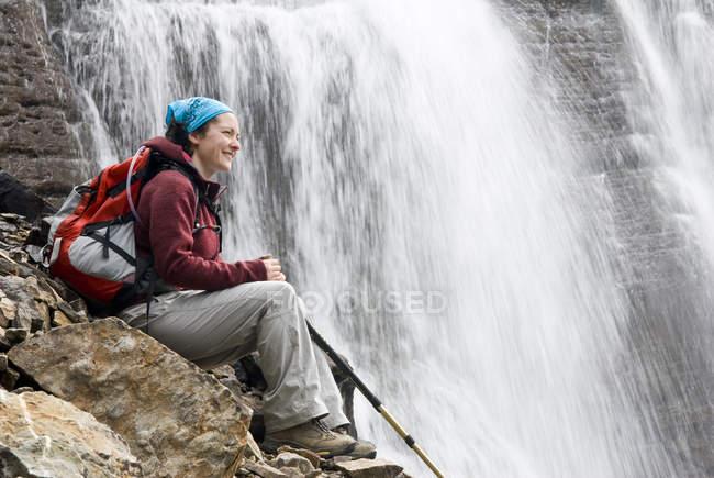 Mujer adulta descansando en Seven Veils Falls cerca del Lago Ohara en el Parque Nacional Yoho, Columbia Británica, Canadá . - foto de stock