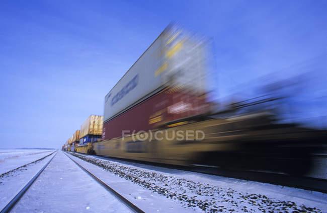 Fracht-Container auf schnell fahrenden Zug mit Motion blur im Winter in der Nähe von Oakbank, Manitoba, Kanada — Stockfoto