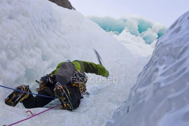 Scalatore di ghiaccio maschio che oscilla asce nella parete rocciosa delle montagne del Ghost River, Alberta, Canada — Foto stock