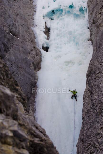 Чоловічий лід альпініст розмахуючи осей в рок обличчя гори привид річки, Альберта, Канада — стокове фото