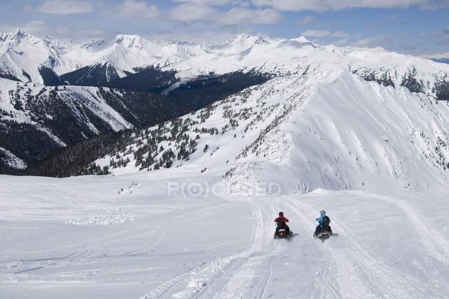 Pair of snowmobilers exploring majestic peaks of Monashees near Valemount, Thompson Okanagan, British Columbia, Canada — Stock Photo