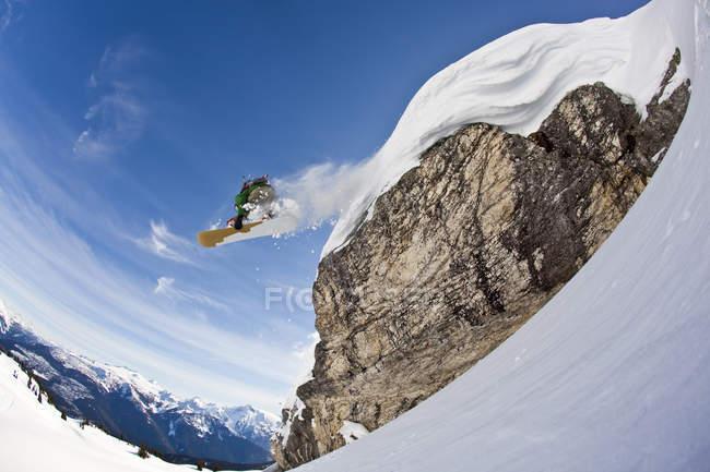 Мужчина сноубордист, спускающийся со снежной подушки, горы Монаши, Вернон, Британская Колумбия, Канада — стоковое фото