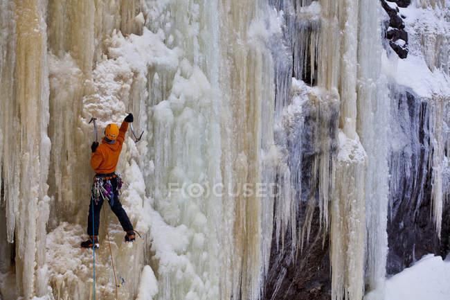 Человек карабкается по пожелтевшей ледяной крутизне около Сент-Раймонда, Квебек, Канада — стоковое фото