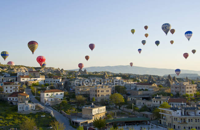 Hot air ballooning over town houses in Goreme, Cappadocia, Turkey - foto de stock