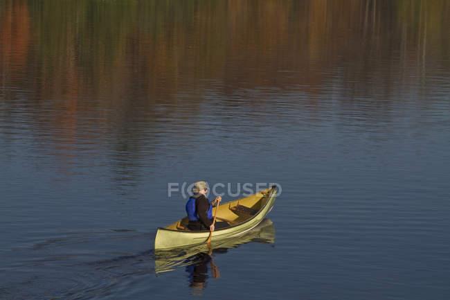 Homme d'âge mûr pagaie canoë sur Oxtongue Lake, Muskoka, Ontario, Canada. — Photo de stock