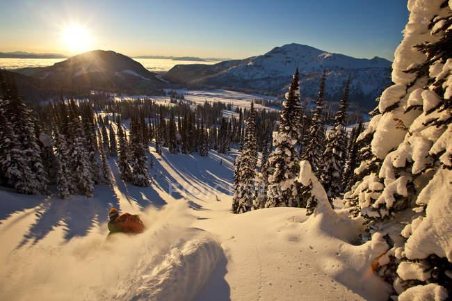 Hombre esquiando en el backcountry en Sol Mountain al atardecer, Monashee Backcountry, Revelstoke, Canadá - foto de stock
