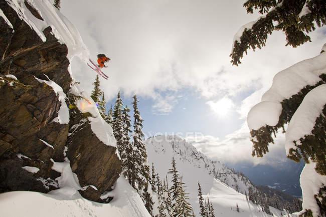 Мужской вольноотпущенник падает со скалы в загородной местности на горном курорте Revelstoke, Канада — стоковое фото