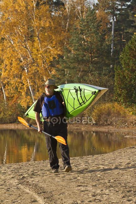 Homme d'âge mûr portant le canot de l'eau, Oxtongue Lake, Muskoka, Ontario, Canada. — Photo de stock