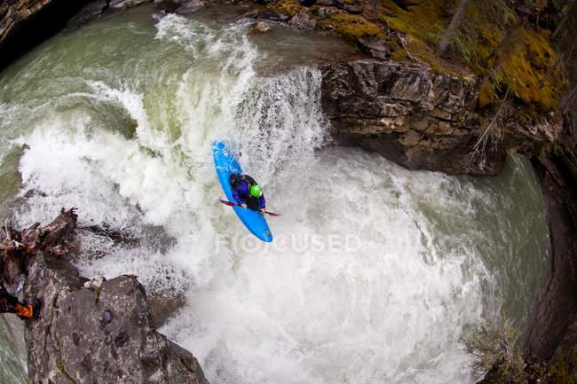 Высокий угол зрения мужчин Байдарочник снижается водопад на Каньон Джонстон, Национальный парк Банф, Канада — стоковое фото