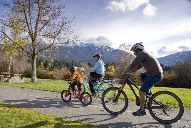 Família, andar de bicicleta ao longo da trilha perto do centro de recreação Meadow Park na Colúmbia Britânica, Canadá — Fotografia de Stock