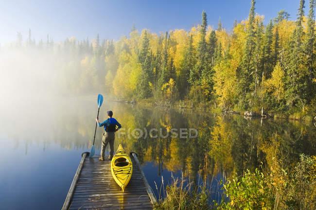 Людину, яка стояла з веслом на док з каяк, озеро Діккенса, Північної провінції Саскачеван, Канада — стокове фото
