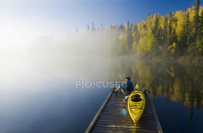 Mann sitzt auf Dock mit Kajak, dickens Lake, Northern saskatchewan, Kanada — Stockfoto