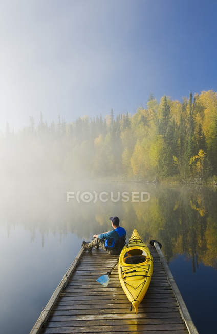 Man sitting on dock with kayak, Dickens Lake, Northern Saskatchewan, Canada — Stock Photo