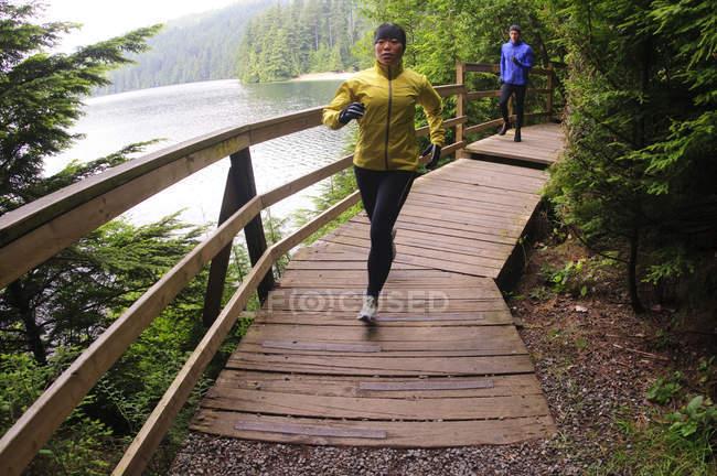 Man and woman running on boardwalk by Sasamat Lake, Belcarra Regional Park, Port Moody, British Columbia, Canada — Stock Photo