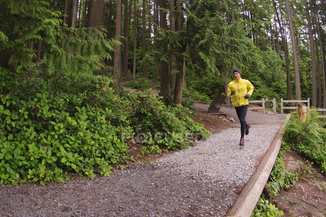 Взрослый мужчина бегает по тропе вокруг озера Сасамат, Региональный парк Белкарра, Порт Муди, Британская Колумбия, Канада — стоковое фото