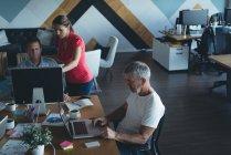 Colegas de trabalho, discutindo sobre o computador na mesa no escritório — Fotografia de Stock