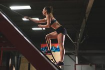 М'язова жінки сходження похилі стіни з мотузкою в тренажерному залі — стокове фото