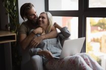 Couple embracing each other while using laptop at home — Stock Photo