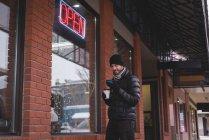 Jeune homme à l'aide de téléphone portable à l'extérieur de la boutique — Photo de stock