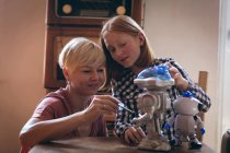 Mother and daughter fixing the robotic toy at home — Stock Photo