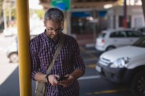 Concentrate man using mobile phone while leaning on pole — Stock Photo