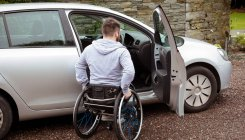 Rear view of disabled man boarding in his car — Stock Photo