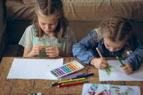 Брати і сестри навчання разом у вітальні на дому — стокове фото