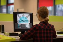 Jeune femme à l'aide d'un pc de bureau dans la bibliothèque — Photo de stock