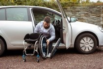 Disabled young man holding wheelchair while getting out of a car — Stock Photo