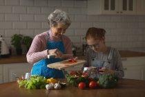 Abuela y nieta cortar verduras en cocina en casa - foto de stock