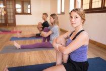 Grupo de personas que realizan ejercicio de yoga juntos en el gimnasio - foto de stock