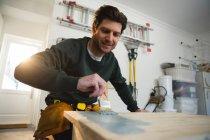Hombre carpintero pintando un cuadro en el taller - foto de stock