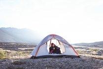 Mann bei Kaffee im Zelt an einem sonnigen Tag — Stockfoto