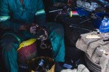 Mechanic repairing auto parts in garage — Stock Photo