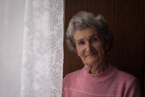 Portrait de femme âgée debout près de la fenêtre à la maison — Photo de stock