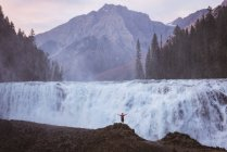 Rear view of man standing with arms outstretched near waterfall — Stock Photo