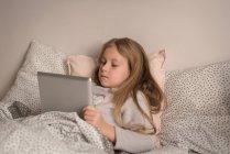 Fille en utilisant tablette numérique dans la chambre à coucher à la maison — Photo de stock