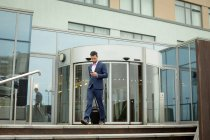 Businessman using mobile phone in hotel premises — Stock Photo