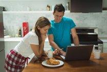Pareja usando portátil y teléfono móvil en casa arte de la cocina - foto de stock
