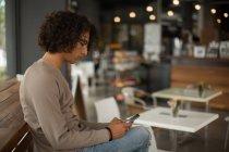 Hombre joven con teléfono móvil en el restaurante - foto de stock