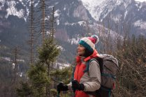 Thoughtful woman standing with backpack and hiking pole during winter — Stock Photo