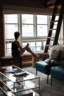 Femme attrayante regardant par la fenêtre à la maison — Photo de stock