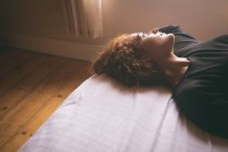 Donna premurosa sdraiata sul letto in camera da letto a casa — Foto stock