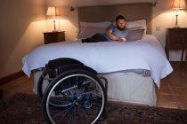 Homme handicapé utilisant un ordinateur portable dans la chambre à coucher à la maison — Photo de stock