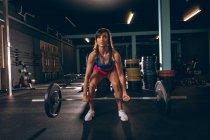 Подходящая женщина поднимает штангу в спортзале — стоковое фото