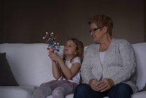 Grand-mère et petite-fille jouent avec le modèle de molécule dans le salon à la maison — Photo de stock