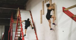 Muscular couple climbing a climbing wall in the gym — Stock Photo